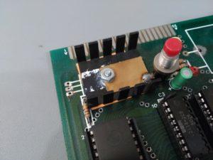 Detalle de zona regulador de tensión y botón de reset